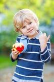 Lustiger blonder Kinderjunge, der gesunden Apfel isst Stockbilder