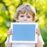Lustiger blonder Kinderjunge, der Tabletten-PC hält, Lizenzfreie Stockfotografie