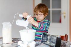 Lustiger blonder Kinderjungen-Backenkuchen zuhause Lizenzfreies Stockfoto