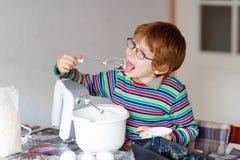 Lustiger blonder Kinderjungen-Backenkuchen zuhause Stockfotografie
