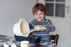 Lustiger blonder Kinderjungen-Backenkuchen zuhause Stockbild