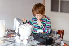 Lustiger blonder Kinderjungen-Backenkuchen zuhause Stockfoto