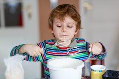 Lustiger blonder Kinderjungen-Backenkuchen zuhause Stockfotos