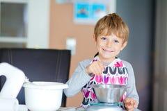 Lustiger blonder Kinderjungen-Backenkuchen zuhause Lizenzfreies Stockbild