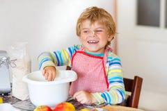 Lustiger blonder Kinderjungenbacken-Apfelkuchen zuhause Stockbilder