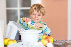 Lustiger blonder Kinderjungenbacken-Apfelkuchen zuhause Stockfoto