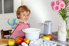 Lustiger blonder Kinderjungenbacken-Apfelkuchen zuhause Lizenzfreie Stockfotografie
