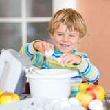 Lustiger blonder Kinderjungenbacken-Apfelkuchen zuhause Stockbild