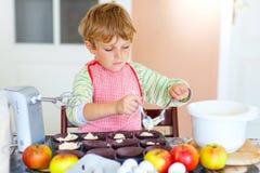 Lustiger blonder Kinderjungenbacken-Apfelkuchen zuhause Stockfotos