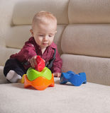 Lustiger blonder Kleinkindjunge, der auf dem Sofa sitzt Stockbild