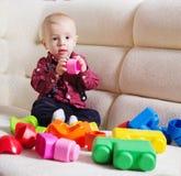 Lustiger blonder Kleinkindjunge, der auf dem Sofa sitzt Lizenzfreies Stockfoto