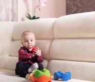 Lustiger blonder Kleinkindjunge, der auf dem Sofa sitzt Stockfoto