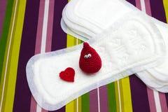 Lustiger Bluthäkelarbeittropfen und Herz mit gesundheitlichen weichen Auflagen der Menstruation, Serviette Frauenhygieneschutz Kr stockfotografie
