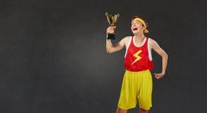 Lustiger dünner Kerl im Sport kleidet mit einer Meisterschaftsschale in seinem Lizenzfreies Stockfoto