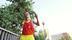 Lustiger dünner Kerlfreak in der Sportkleidung geht, bevor er rüttelt