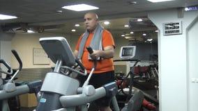 Lustiger dicker Mann, der Übungen auf dem Ellipsoid in der Turnhalle tut stock footage