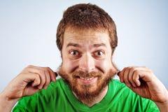 Lustiger dummer Mann, der seinen haarigen Bart ergreift Stockbilder