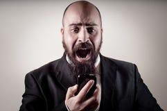 Lustiger eleganter bärtiger Mann, der am Telefon schreit Stockbild