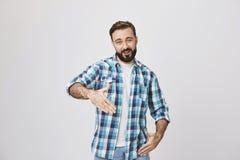 Lustiger erwachsener bärtiger Mann mit modischem Haarschnitt und dem karierten Hemd, die Robotergesten macht oder das Pochen steh stockbilder