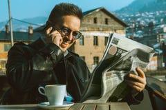 Lustiger erwachsener Mann las Unterhaltungstelefon der Zeitung und trinkendes coffe lizenzfreies stockfoto