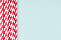 Lustiger festlicher heller abstrakter Hintergrund - gestreifte rote Cocktailstrohe auf Pastellsüßigkeitsminze färben Hintergrund Lizenzfreies Stockbild