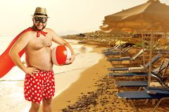 Lustiger fetter bärtiger Mann im Urlaub auf einem Sommerstrand stockbild