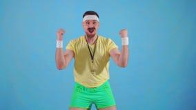 Lustiger froher männlicher Trainer von den achtziger Jahren mit einem Schnurrbart und Gläsern mit einer Stoppuhr stock footage