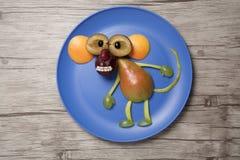 Lustiger Fruchtaffe auf Platte und hölzernem Hintergrund Lizenzfreies Stockbild