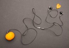 Lustiger fruchtiger Musikspieler: Kopfhörer, die von der Mandarine auf einem schwarzen Hintergrund kommen Lizenzfreies Stockfoto