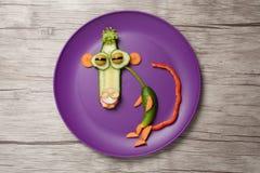 Lustiger Gemüseaffe auf purpurroter Platte und Tabelle Lizenzfreie Stockfotografie