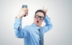 Lustiger Geschäftsmann, der auf einem Smartphone sich fotografiert Stockfotografie