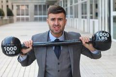 Lustiger Geschäftsmann, der schwere Gewichte anhebt stockfotografie