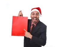 Lustiger Geschäftsmann in Weihnachts-Sankt-Hut, der rote Einkaufstasche im Dezember und Verkauf des neuen Jahres hält Lizenzfreie Stockbilder