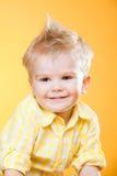 Lustiger glücklicher lächelnder kleiner Junge im Gelb Lizenzfreie Stockbilder