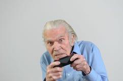 Lustiger Großvater, der ein Videospiel auf Konsole spielt lizenzfreie stockfotografie