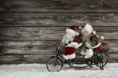 Lustiger hölzerner Weihnachtshintergrund mit zwei Weihnachtsmann auf einem bicy Stockfoto