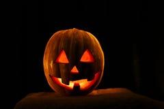 Lustiger Halloween-Kürbis lokalisiert auf einem schwarzen Hintergrundglühen von Stockbild