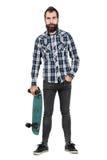 Lustiger Hippie mit tragendem Skateboard in einer Hand, die Kamera betrachtet Lizenzfreie Stockfotos
