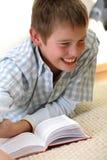 Lustiger Junge, der auf dem Fußboden erlernt Stockbild