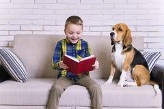 Lustiger Junge, der ein Buch mit einem Spürhund liest Stockfotografie