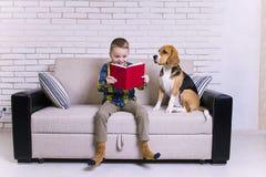 Lustiger Junge, der ein Buch mit einem Spürhund liest Lizenzfreie Stockfotografie