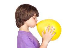 Lustiger Junge, der einen gelben Ballon sprengt lizenzfreie stockfotos