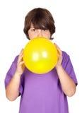 Lustiger Junge, der einen gelben Ballon sprengt Stockbild