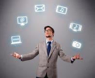 Lustiger Junge, der mit Ikonen der elektronischen Geräte jongliert Lizenzfreies Stockfoto