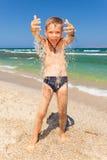 Lustiger Junge, der mit Sand auf dem Strand spielt Lizenzfreie Stockfotografie
