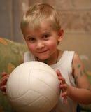 Lustiger Junge mit dem geheimnisvollen Anblick, der weiße Kugel anhält Lizenzfreies Stockbild