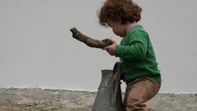 Lustiger Junge mit der grünen Strickjacke, die draußen mit altem Pitcher spielt stock footage