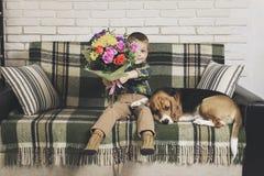 Lustiger Junge mit einem Blumenstrauß von Blumen und von Hundspürhund Stockfoto