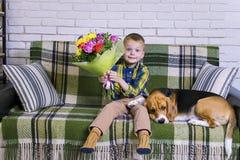Lustiger Junge mit einem Blumenstrauß von Blumen und von Hundspürhund Stockfotos