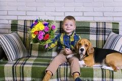 Lustiger Junge mit einem Blumenstrauß von Blumen und von Hundspürhund Lizenzfreie Stockfotos